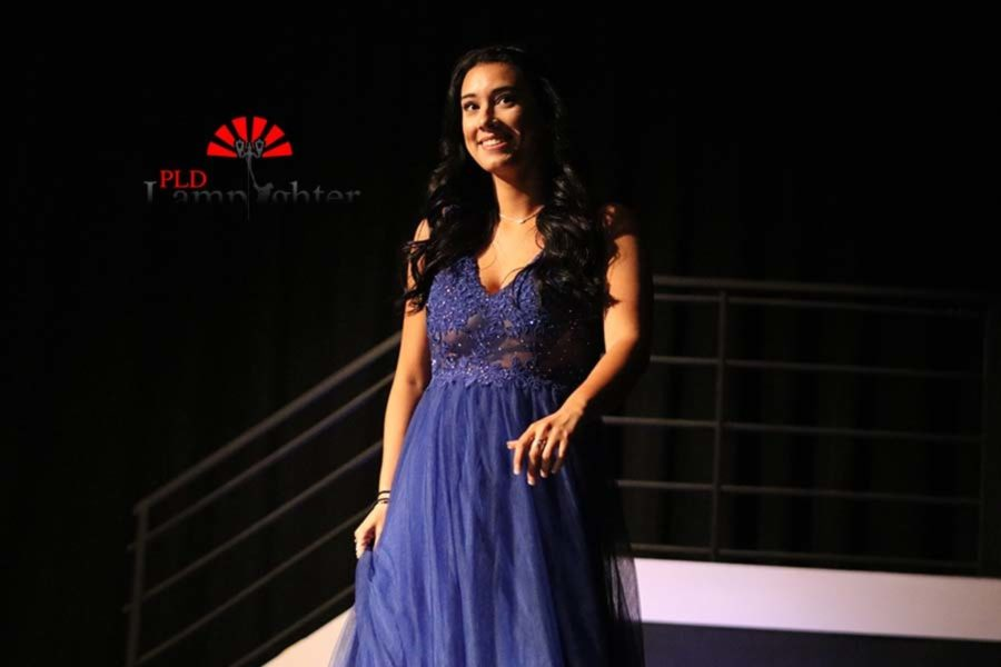 Katrina Contreas smiling to the crowd in a blue prom dress.