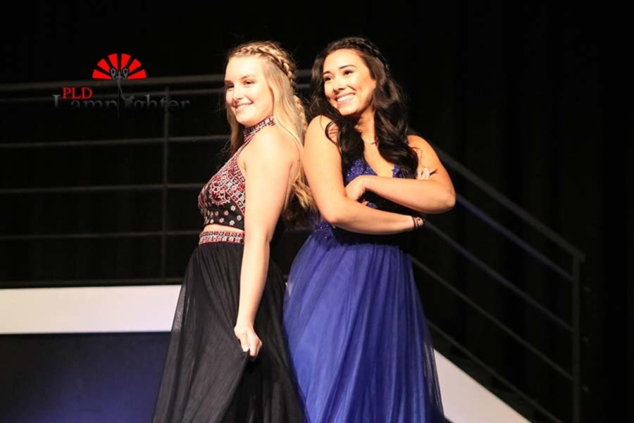 Juniors Grace Mortenson and Katrina Contreas pose side by side in prom dresses.