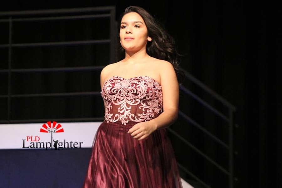 Socorro Rodriguez walks out on stage in a formal gown.