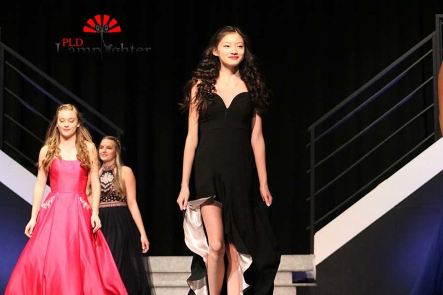 Celino Luo leads her group while wearing a strapless black prom dress.