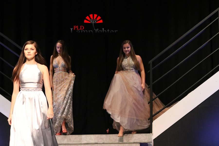 Sophomores of the fashion marketing class walk out modeling prom dresses.
