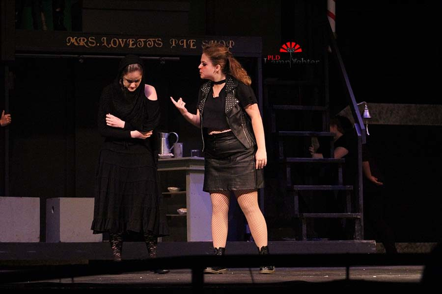 Mrs. Lovett (Mackenzie McConnell) shoos away the beggar woman (Emma Draper) from her shop.
