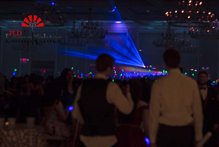 Multi colored lights shining above the dance floor as students enter.