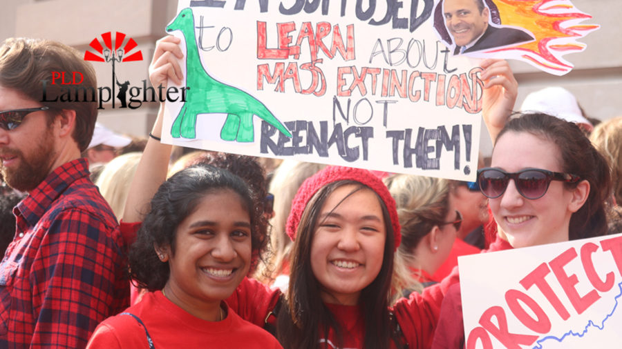 Dunbar students Divya Sunderam, Kelly Chen, and Erin Markel pose for a photo with their signs.