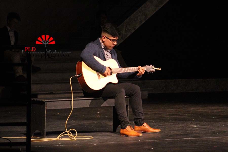 Frankiee Rodriguez plays guitar during a performance at the talent show.