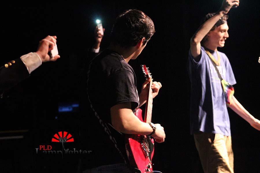 Junior Jack Burton playing the guitar as Max Taylor sings.