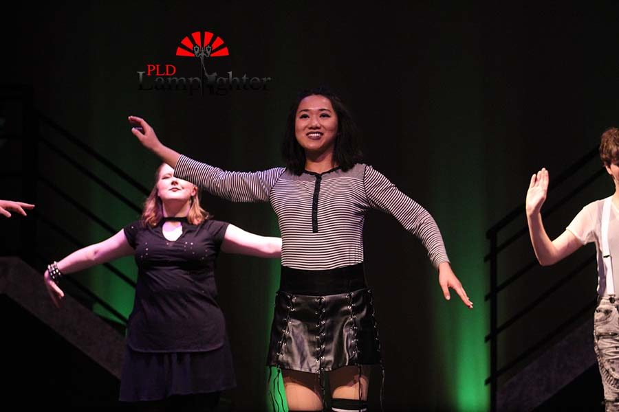 A member of the ensemble (Angela Fu) waves her arms as a part of the dance.