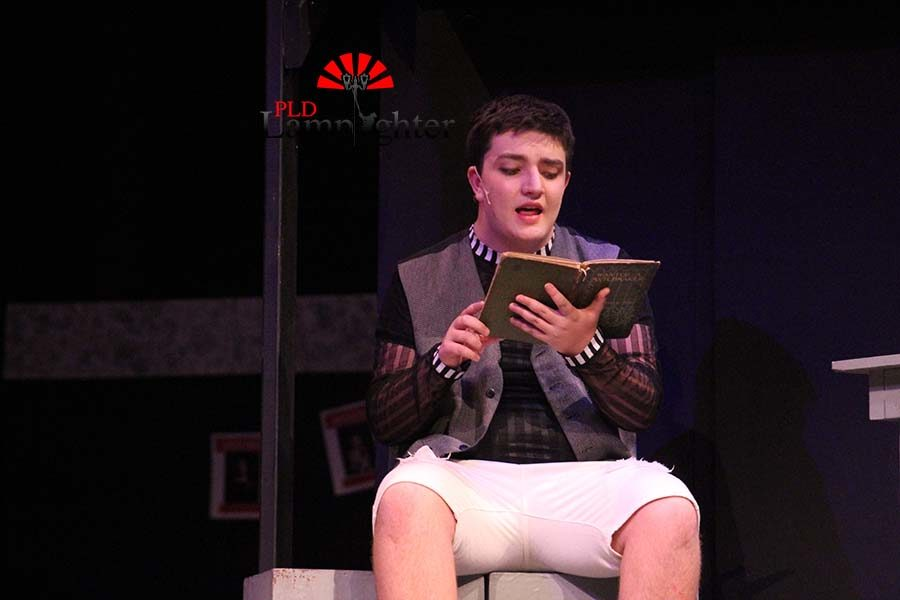The Beadle (played by freshman Nick Clevenger) sings a song from a book.