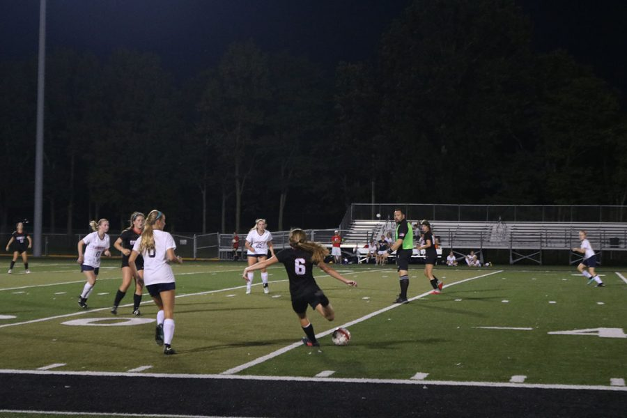 Gracie Logan #6 makes her pass through her opponents, hoping it will land at her teammate's feet.
