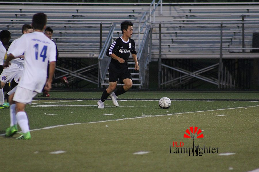 Kevin Jing, #8 pushes the ball up the field towards the goal.