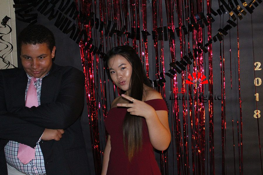 Sandy Tang and Ben Rains are the first to pose with the photo booth backdrop.