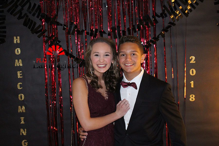 Olivia Doyle and Grayson Rulon show off their matching outfits in front of the homecoming backdrop.