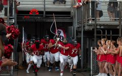 In 2018, Dunbar's football team showing their school spirit as they rush to the field with the school flag.