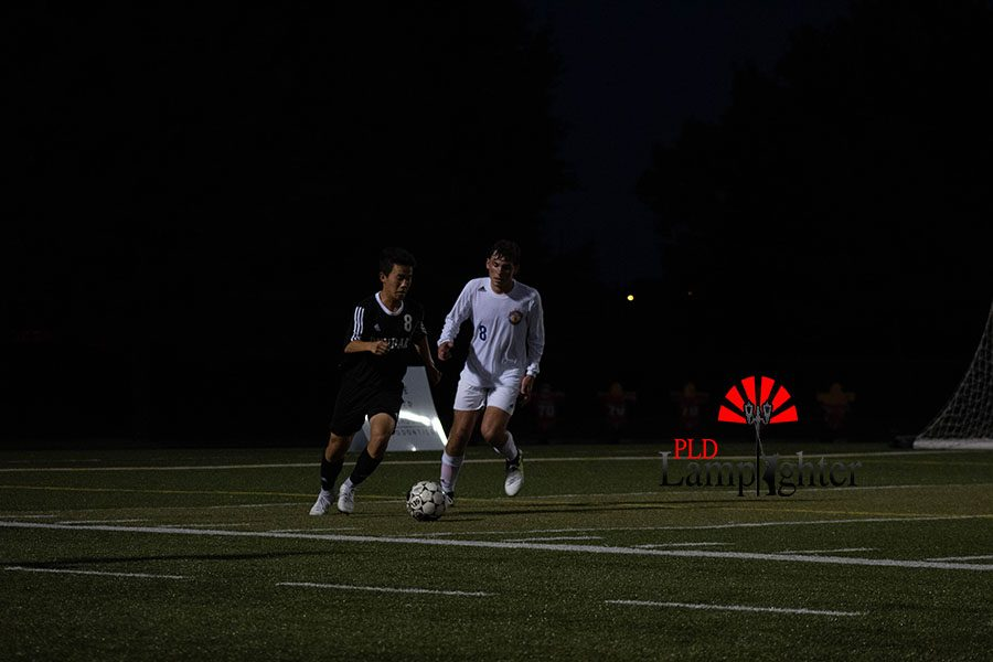#8 Kevin Jing fights for the ball by trying to push it further away from his opponent.