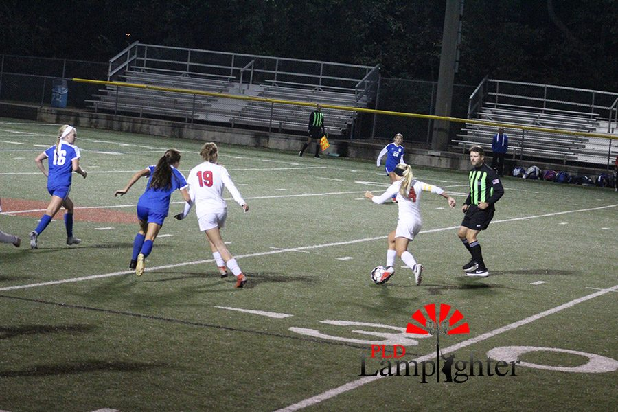 #4 Audrey Rawls dribbles the ball down field while #19 Mary Bretz gets physical with an opposing player to keep her away from the ball.