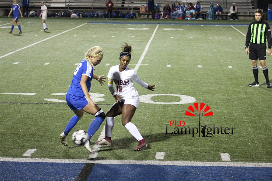 #15 Meron Roach attempts to stop an attacker from getting down the field and scoring.