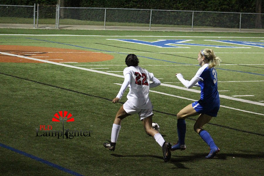 #22 Isha Joshi pushes off a opposing player to get to the ball first and have a chance to attack up field.