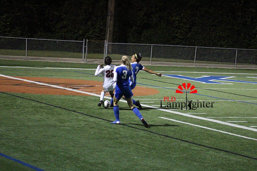 #22 Isha Joshi attempts to move the ball around the enemy team to setup a goal kick.