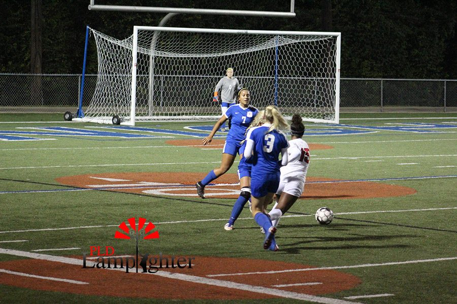 #15 Meron Roach cuts the ball into the middle of the field for a shot opportunity on goal.