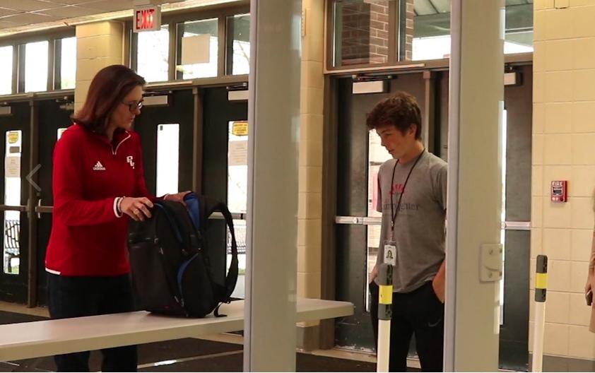 Principal Betsy Rains helps a student through the new metal detectors at PLD