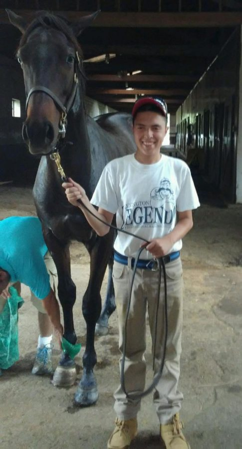 Miguel Ramirez standing with one of the many horses he tends to at his uncle's farm.
