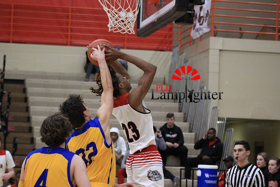 #23 Tim Hall attempts a layup while a Henry Clay defender tries to block it.