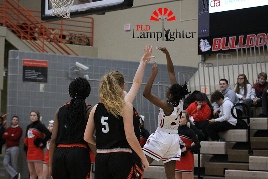 #21 Aziah Campbell drives the rim and shoots a layup before the defense can block it.