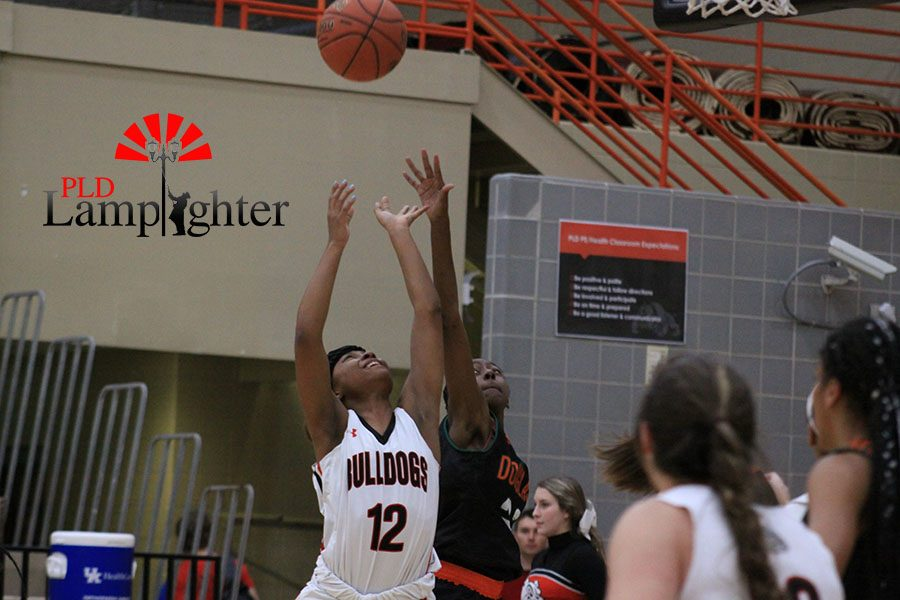 #12 DelTarria Jackson goes up for a rebound against a Fredrick Douglass defender.