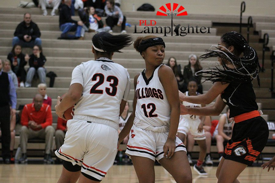 #12 DelTarria Jackson passes the ball to #23 Tanaya Cecil to try and throw the defense off on where the ball is going.