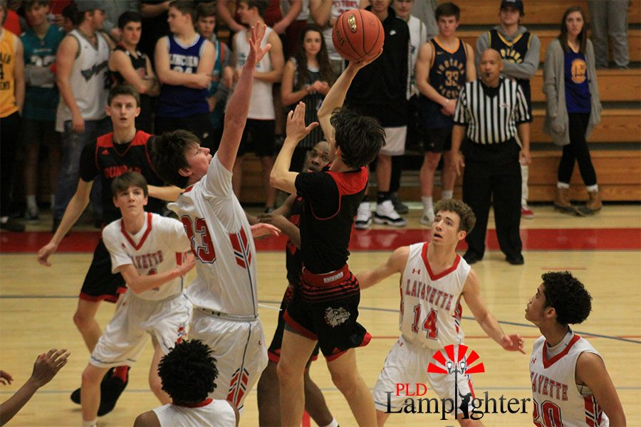 #0 Grayson Shively attempts a shot near the free-throw line over Lafayette defender.