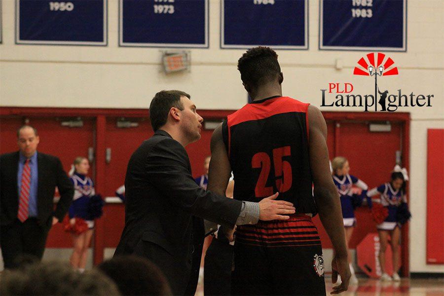 Coach Barnes talking to #25 Rabbi Kamona before the start of the game.