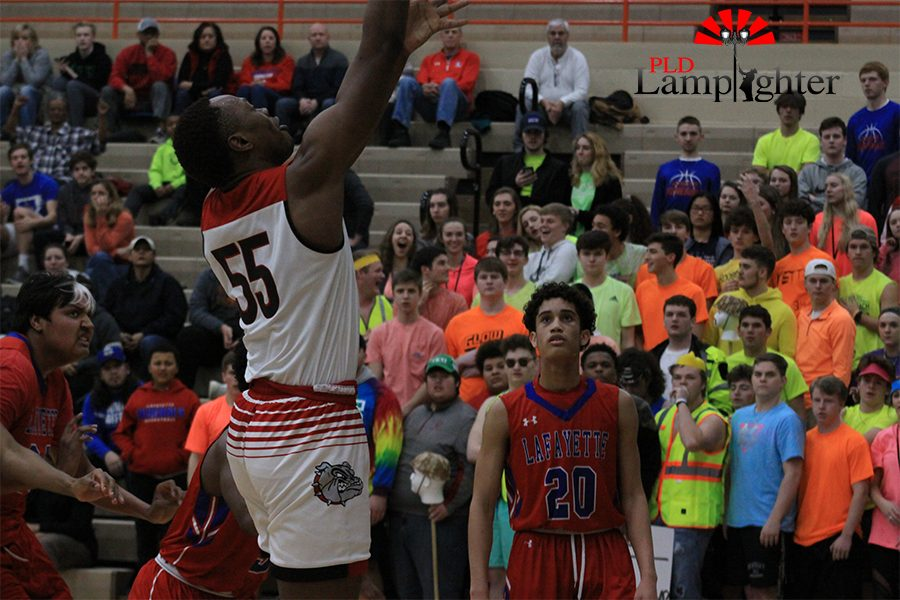 #55 Lionel Kumwimba moves past defenders for a layup.