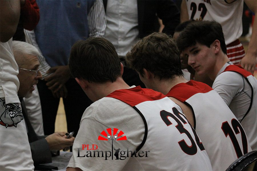 Coach Chalk talking to players on the bench during a timeout.