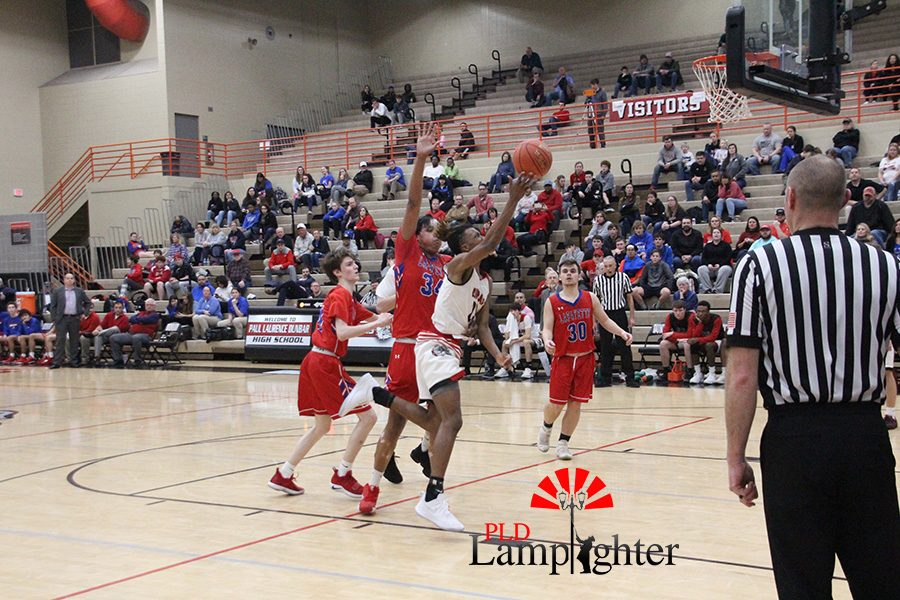 #23 Tim Hall drives the lane to attempt a layup while being heavily covered by Lafayette players.
