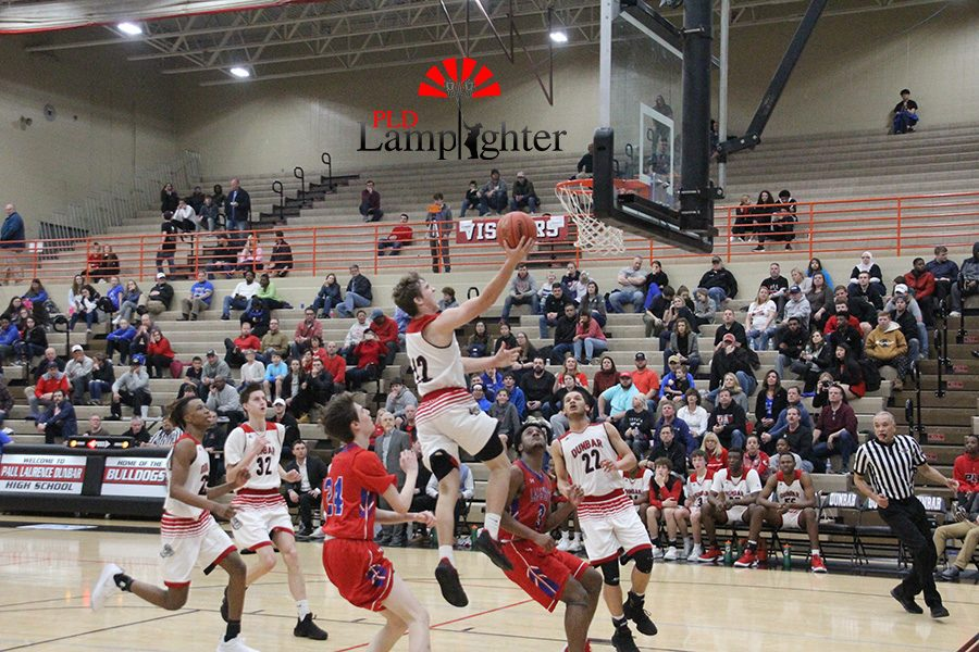 #12 Jared Gadd goes for a layup while being guarded by a Lafayette player.