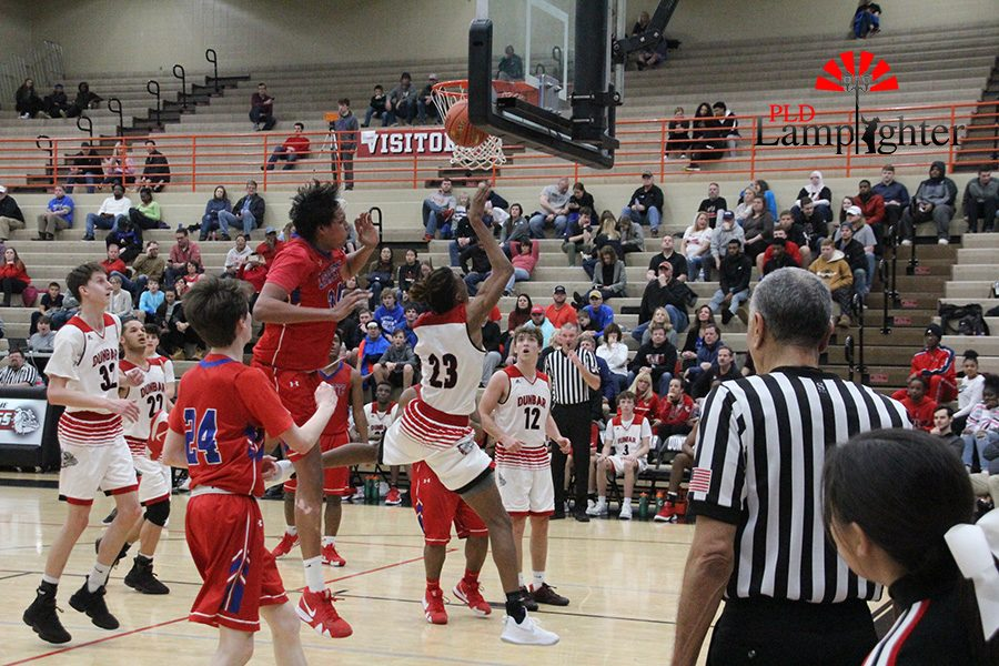 #23 Tim Hall attempts a layup while being guarded by Lafayette players.