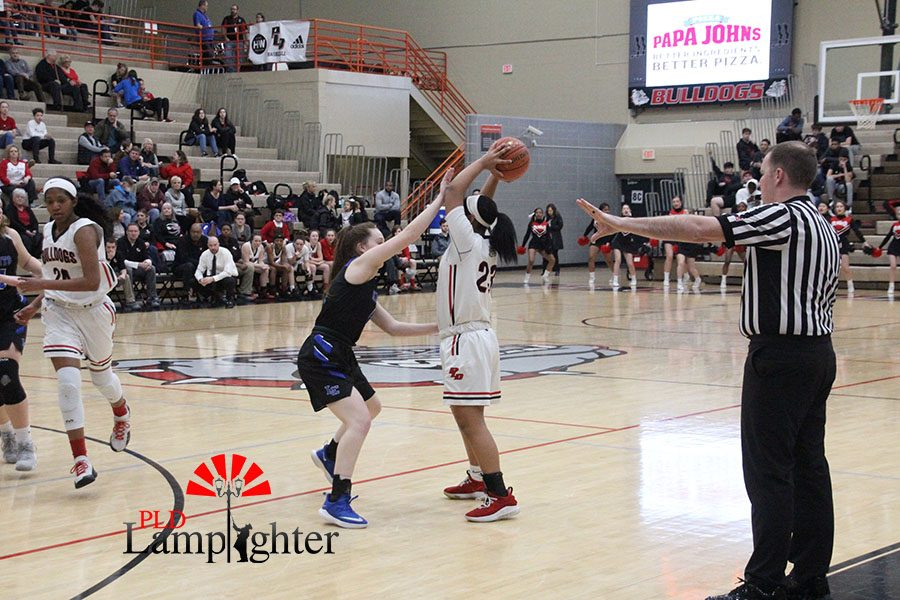 #23 Tanaya Cecil preparing to pass the ball across the court.