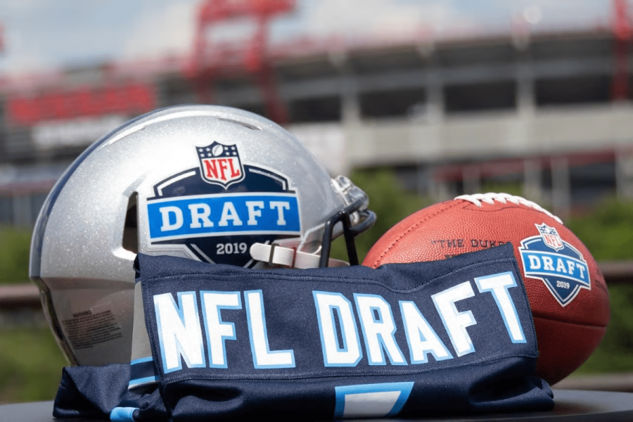 A helmet with the 2019 NFL Draft Logo lying next to an NFL Draft jersey and an NFL Draft football.