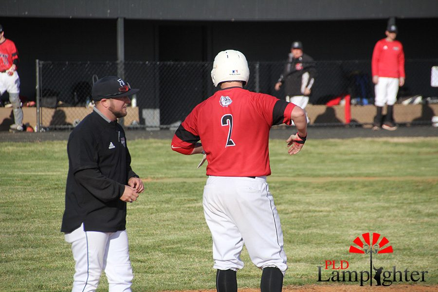 #2 Griffen Brown talks to the first base coach when he gets on first base after a hit to center field.