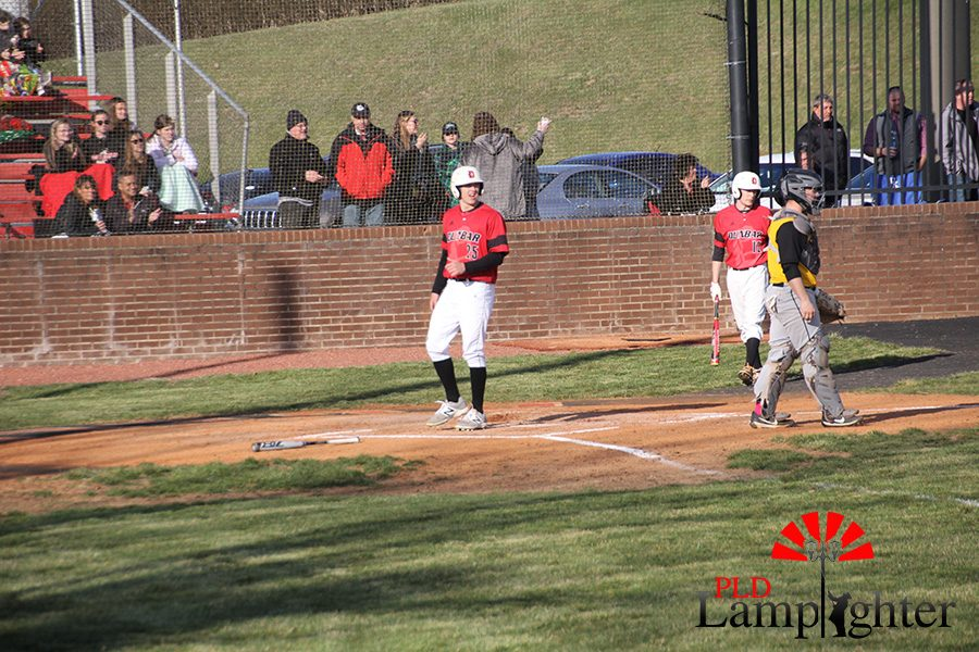 #25 Jared Gadd walks on home base to score a run after a big hit by #10 Adam Talwalkar.