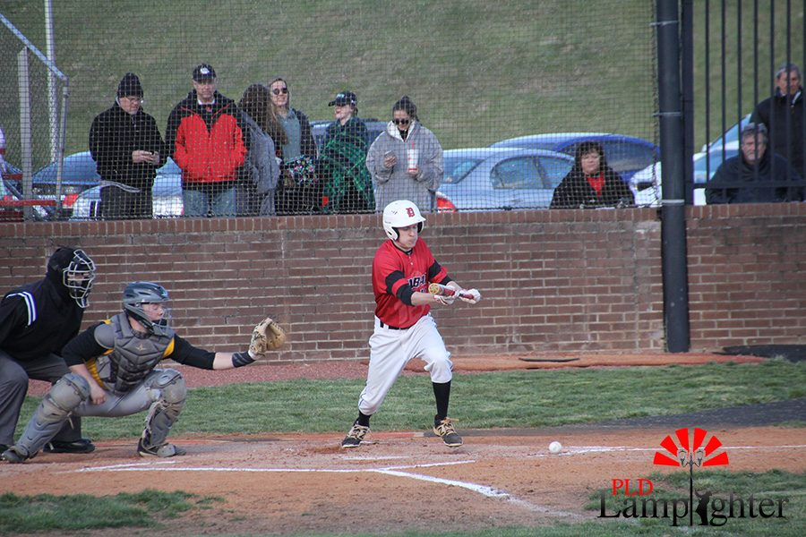 #12 	Kenneth Henderson bunts the ball with a teammate on third to attempt to get a run.