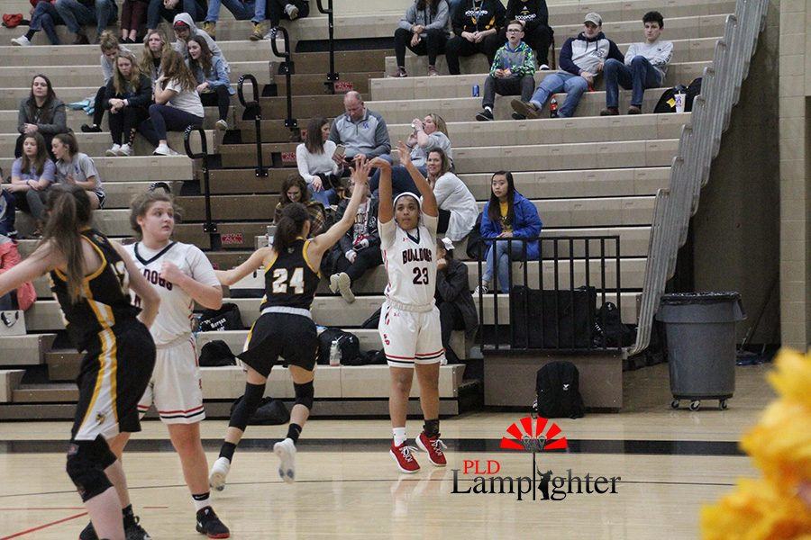 #23 Tanaya Cecil shoots from behind the line to get a three point shot.