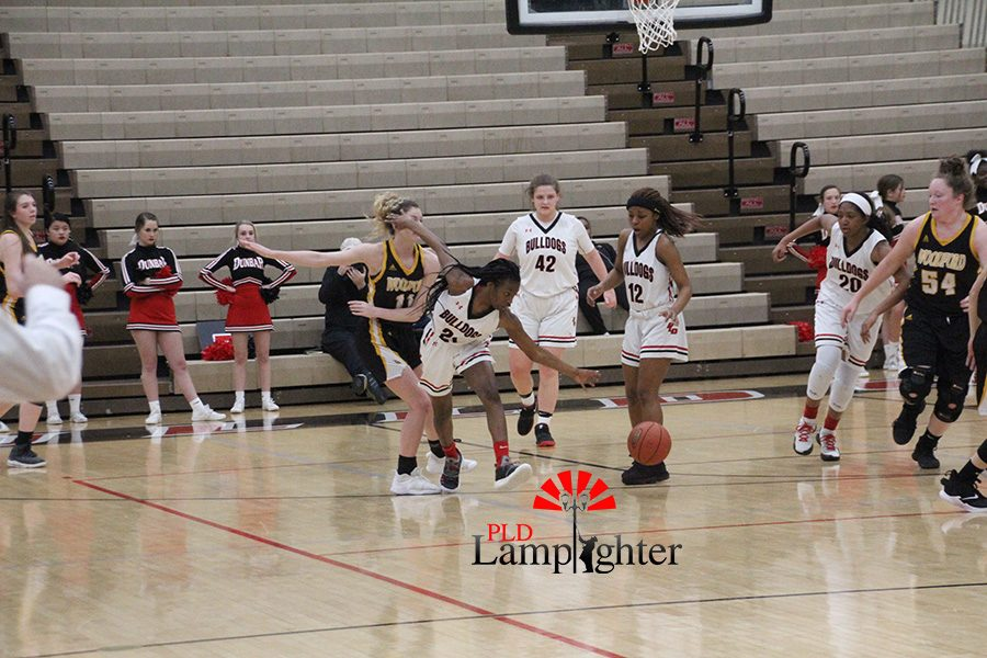 #21 Aziah Campbell reaches for the ball, in an attempt to gain possession before the other team.