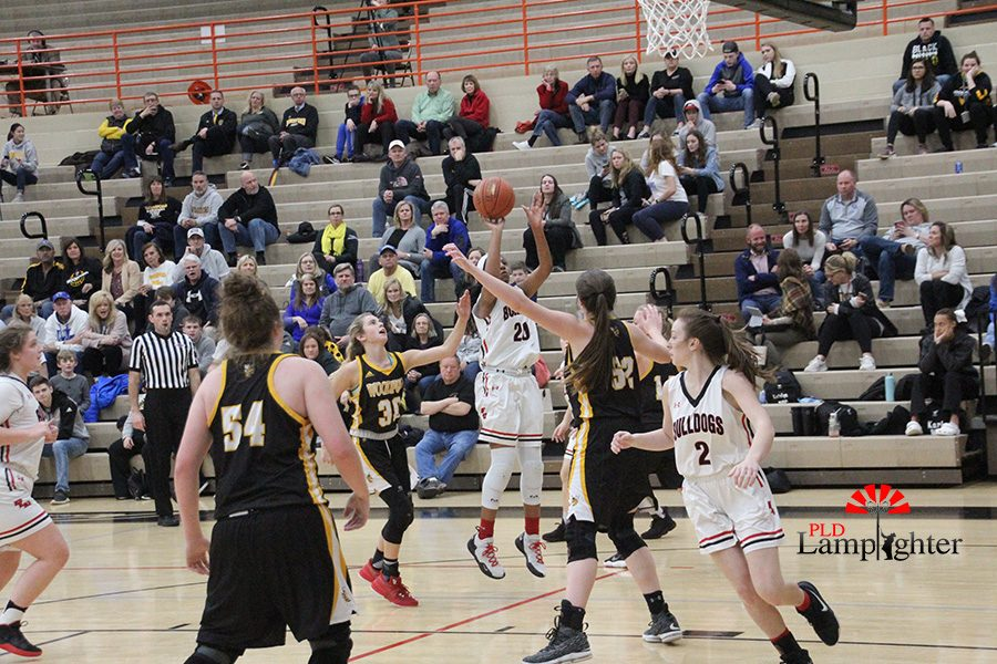#20 Cheyenne Fullwood shoots a jump shot while being heavily covered by Woodfords defense.