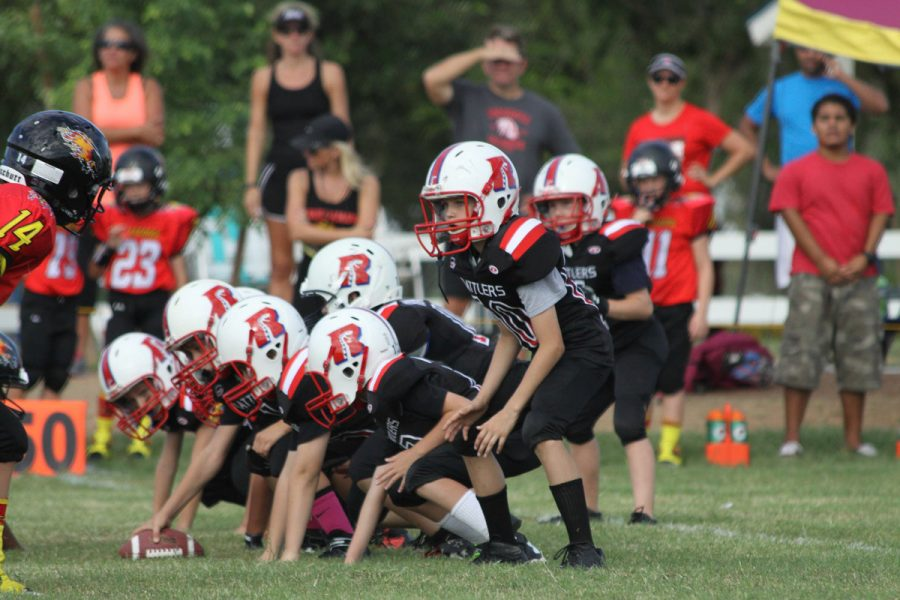 A Pop Warner Football team lining up on offense about to run a play. The front line is displaying the now banned 3-point stance.