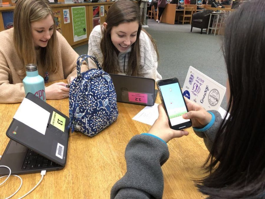 Sophomores Elizabeth Fitzpatrick and Olivia Wells, with freshman Emma Daman using multiple devices.