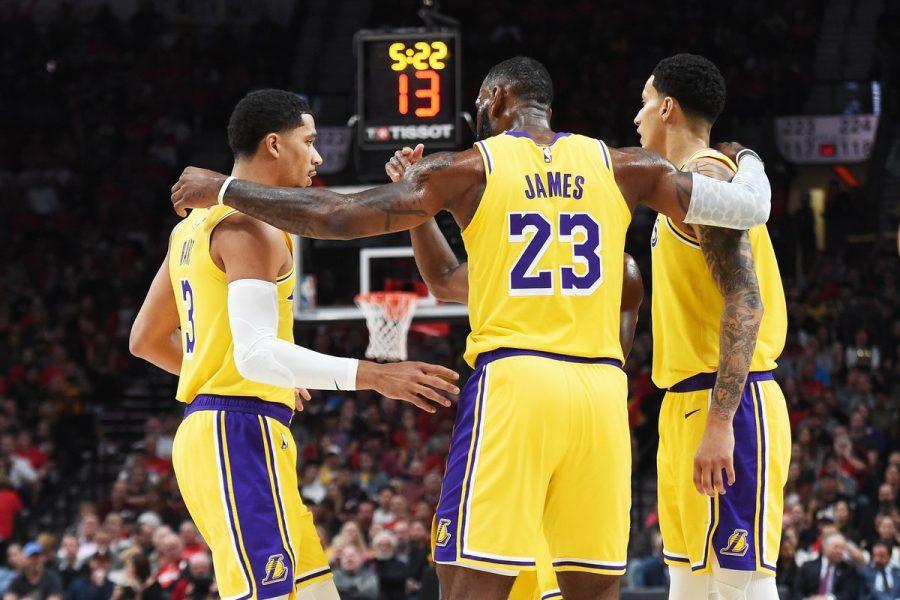 LeBron James standing with team mates Rajon Rondo and Kyle Kuzma.