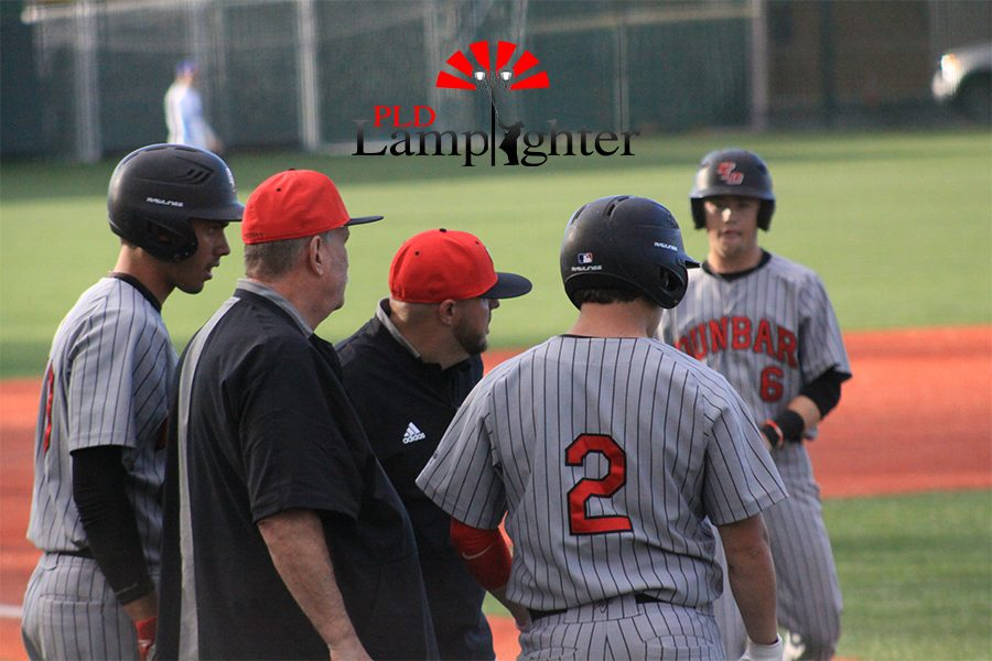 Coaches advising base runners while the opposing team changes pitchers.