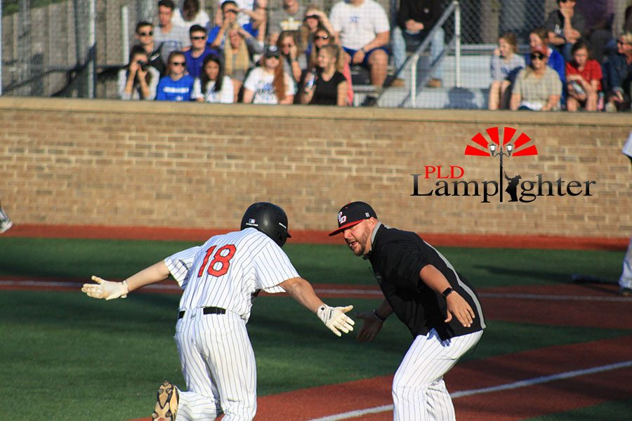 #18 Cameron Baughman high fiving Coach Deaton on his way to home plate.