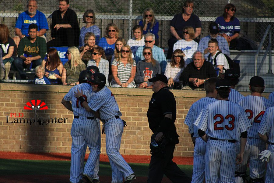 #18 Cameron Baughman celebrating with teammates after a homerun.